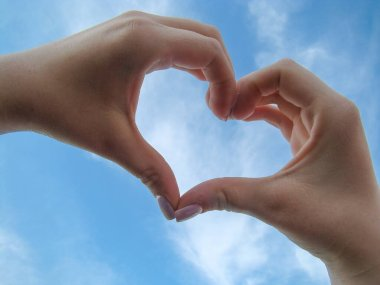 hands of a young woman with heart symbol, on blue sky background