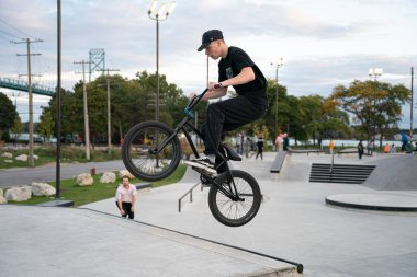 skaters are practicing tricks in an outdoor skate park in Detroit Michigan