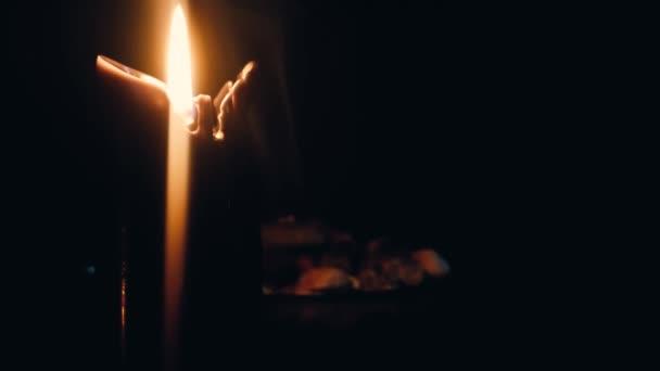 Rituális viaszgyertya. Egy füstölgő edény. Közelkép. Egy sötét szoba.
