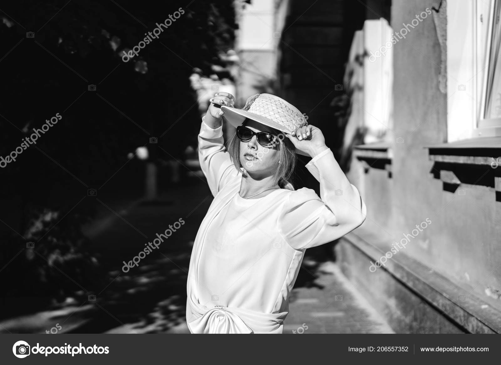 Black and white view of pretty woman in white vintage dress hat and sunglasses posing on street photo by