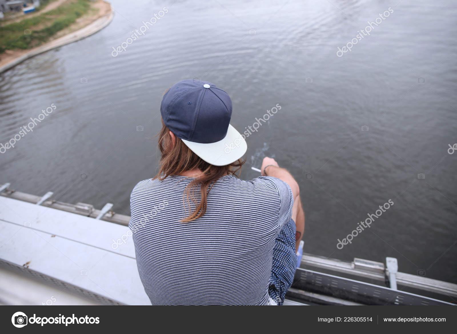 Muž kouří a sedí s jeho zády v baseballové čepici na okraji mostu ve výšce  nad řekou. Moskva. 27.07.2018– Stock Editorial Fotografie aa3189175b