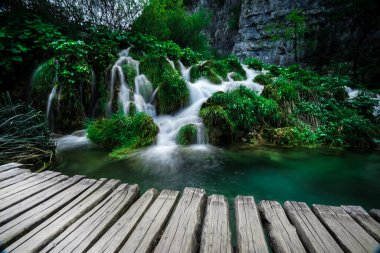Low angle, long exposure show of waterfall, lake and boardwalk in Plitvice national park