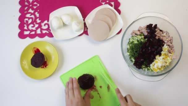 Kuchař kusy vařené řepy na prkně. V blízkosti v nádobí jsou další přísady pro vaření cukrové řepy, slepičí vejce, salám a okurku. Pohled shora