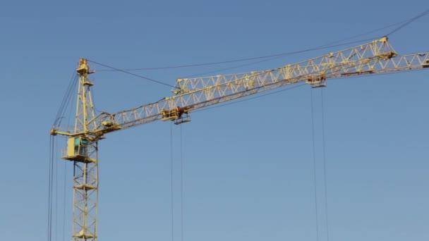 Šipky stavební věžové jeřáby proti modré obloze.