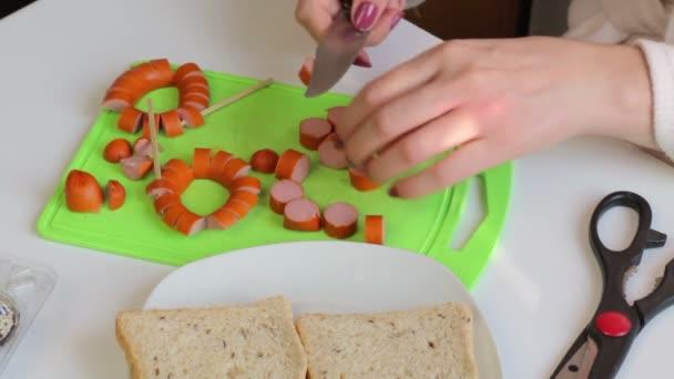 Žena na vaření. Řezy z klobásy. Snídaně párky, Křepelčí vejce, bylin a zeleniny. Ingredience jsou na stole.