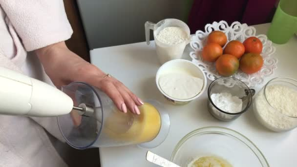 Vaření sušenky roll plněné ricottou a mandarinky. Žena dává v mixéru slepičí vejce s cukrem. Dalšími složkami leží vedle sebe na stole.