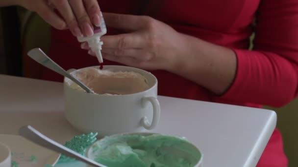 женщина добавляет каплю красителя из трубки плавленого сыра крем для смазывания торт раскраски