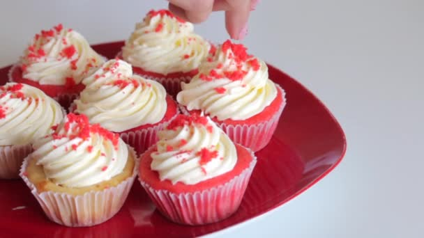 Woman preparing cupcake red velvet. Sprinkle cream with crumbs. The finished cakes are on the plate.