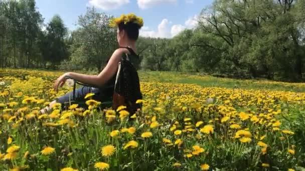 Egy lány ül egy piknik széket. Tavasszal rét, borul virágos pitypang. A fej a koszorút a pitypang. Napsütéses tavasz a parkban.