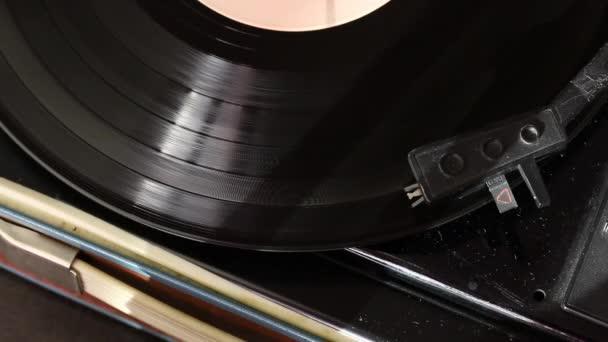 Vinylové Spiny na přehrávači. Jehlovou hlavu přehrávače se pohybuje podél trati. Všechno je pokryto prachem. Pohled shora.