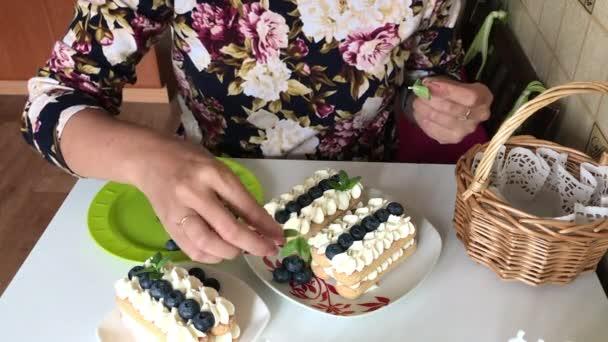 Eine Frau verziert Kuchen aus savoiardi-Keksen und Sahne. dekoriert mit Blaubeeren und Minze.