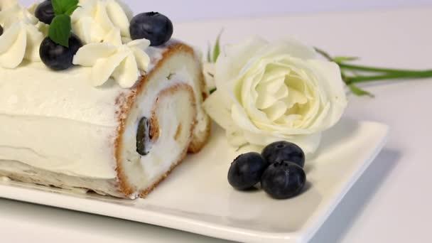 Houbovka potažená smetanou a zdobená sušenými borůvkami a čerstvým mátovou listou. Nedaleko leží bílá růže.