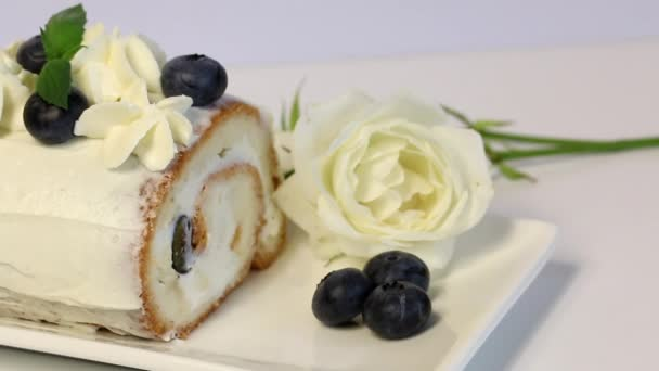 Sponge cake coated with cream and garnished with dried blueberries and fresh mint leaves. Nearby lies a white rose. Close-up shot.