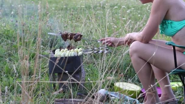 Žena připravuje gril na grilu. Smažené maso a zelenina jsou viditelné na špejlích. Žena upraví špejle a posype kebab vodou.