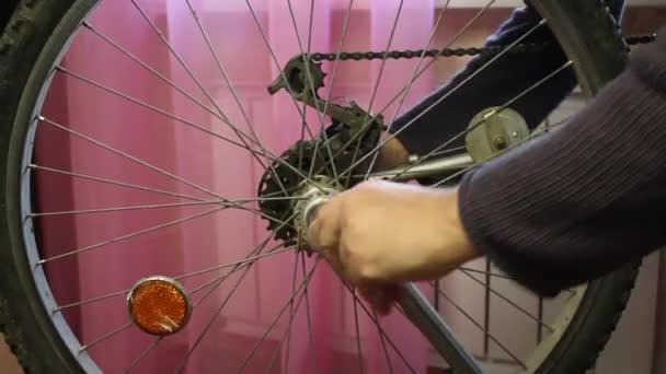 Muž odstraní z kola rychlorozpínací kolo. Vypne výstřednost..
