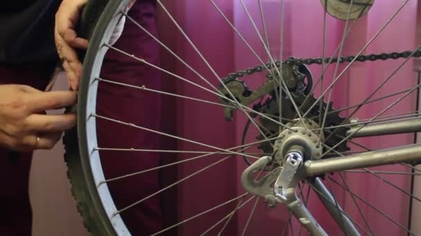 A man removes a tire from a bicycle wheel. Close-up shot.