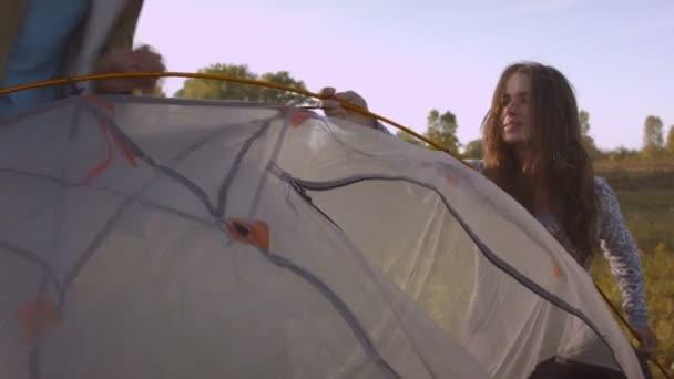 A fiatal pár felállít egy sátrat a hegyi erdőben naplementekor..