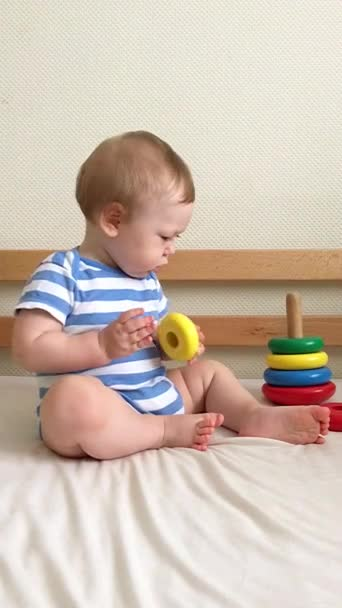 Baby boy playing on the bed with a wooden toy pyramid
