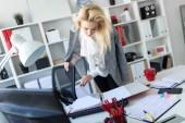 Fotografie Ein junges Mädchen steht in der Nähe ein Tisch im Büro und blättert durch einen Ordner mit Dokumenten