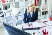 Fotografie Junges Mädchen sitzen am Schreibtisch im Büro und arbeiten mit Dokumenten