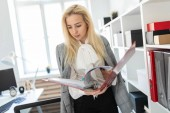 Fotografie Ein junges Mädchen steht in der Nähe ein Rack im Büro und blättert durch einen Ordner mit Dokumenten