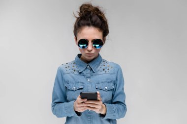 Young brunette girl in round glasses. Hairs are gathered in a bun. Girl with a black phone. The girl is looking at the phone.