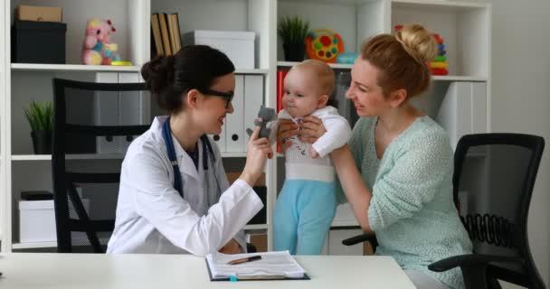 Arzt gibt Baby in weißem Zimmer Spielzeug