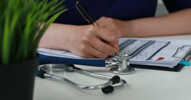 abgeschnittenes Bild von Arzt füllt Papiere Stethoskop