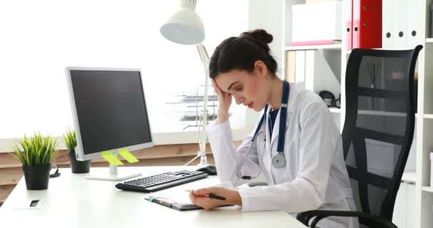 young doctor filling documents with hand on head