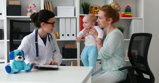 Mutter mit Kind an der Rezeption einer jungen Ärztin