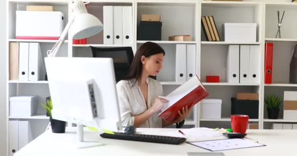 businesswoman in white blouse reading documents in folder