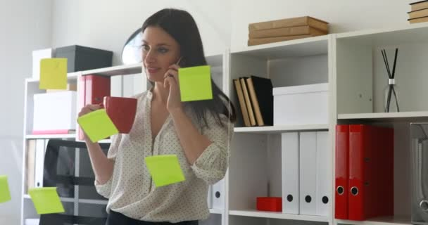 businesswoman in white blouse considering sticky notes on glass and talking on phone