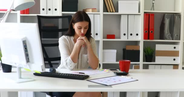 businesswoman in white blouse sitting workplace and looking at camera