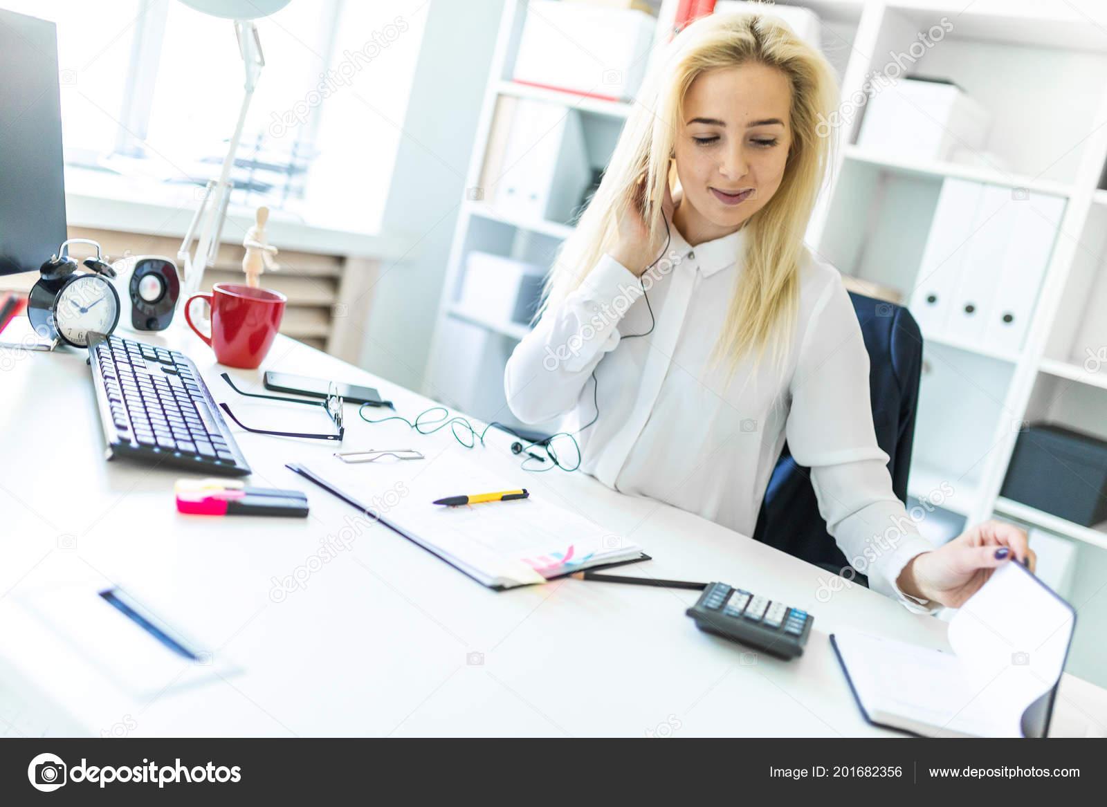 6d3b87a98224 Λεπτή κοπέλα με μια λευκή μπλούζα εργάζεται στο γραφείο. Το κορίτσι έχει  άσπρα μακριά μαλλιά. φωτογραφία