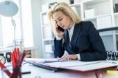 Fotografie Junges Mädchen sitzen am Schreibtisch im Büro, am Telefon zu sprechen und mit Blick auf Dokumente