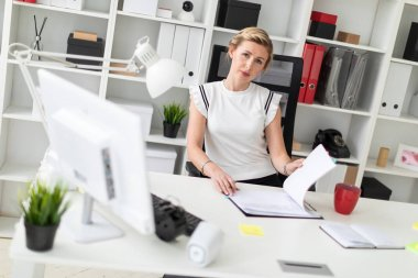 Beautiful young girl with blond hair in a white shirt is working in the office. photo with depth of field stock vector