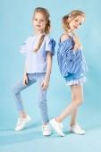 Fotografie Mädchen Zwillinge in hellblauen Kleidern posieren auf blauem Hintergrund.