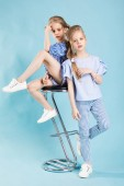 Photo Girls twins in light blue clothes are posing near a bar stool on a blue background.
