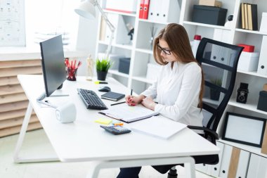 Young girl sitting at the table and working  in office