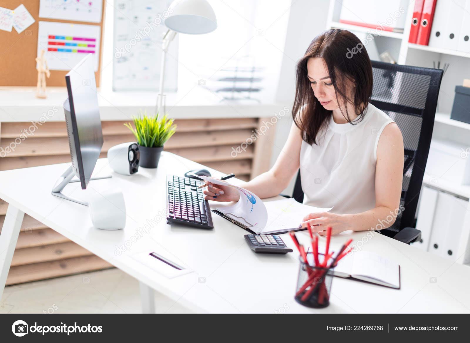 6afdfa5fcb14 Όμορφη νεαρή κοπέλα που εργάζεται σε ένα φωτεινό γραφείο. Νεαρή κοπέλα σε λευκή  μπλούζα και μαύρη φούστα. φωτογραφία