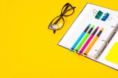 bright pens, glasses and notebook lie isolated on yellow background