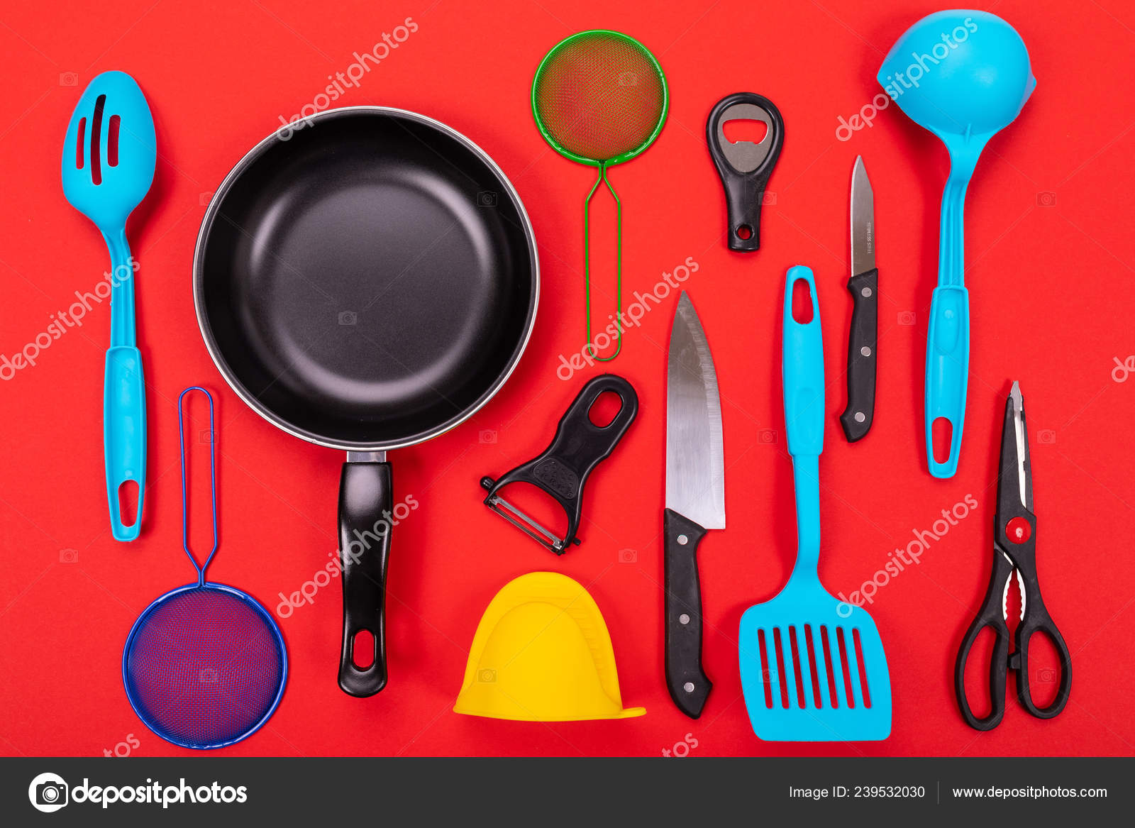 Frying pan with kitchen utensils isolated on red background ...