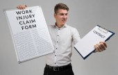 Fotografie young man holding a form with a claim of injury at work and blank contract form isolated on a light background