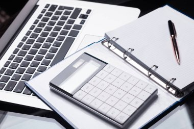 Modern calculator is on a laptop and on an open notebook