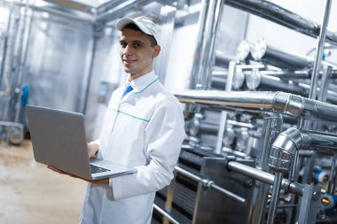 Technologist in a white coat with a laptop in his hands controls the production process in the dairy shop. Quality control at the dairy plant stock vector