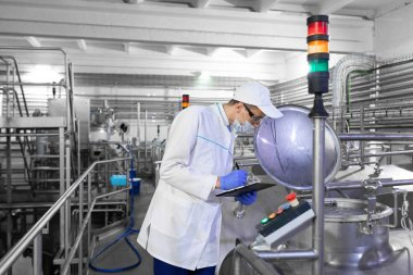 Technologist in white coat and mask makes notes with pen in sheet at dairy plant. Profile view dairy factory worker wearing overall standing at production department and controlling technological stock vector