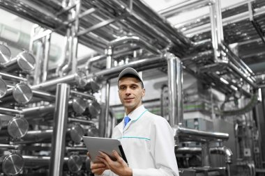 Technologist with grey tablet in his hands make a set up of the production line while standing at the department of dairy factory stock vector