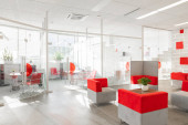 Photo Minsk, Belarus - May 23, 2019: Corner of modern office with white walls, gray floor, open space area with red-white armchairs and rooms behind glass wall