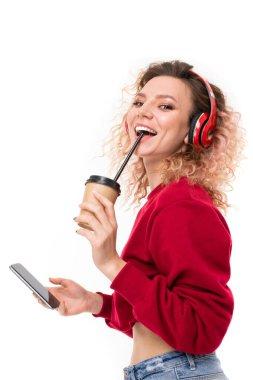 beautiful blonde girl with headphones, phone and coffee