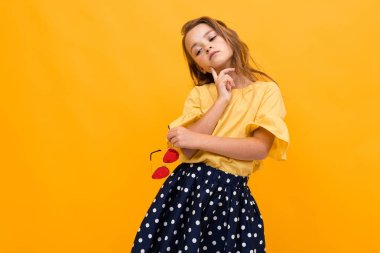 cute fashionable girl posing against orange